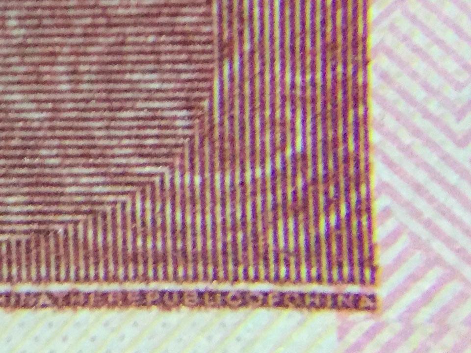 以 iPhone6 加「2號 超廣角鏡頭組 的微距鏡頭」拍攝 100元 正面右下角的防偽線標示後的邊角原吋截圖